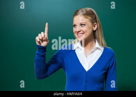 Young teacher is pointing in front of blackboard. - Stock Photo