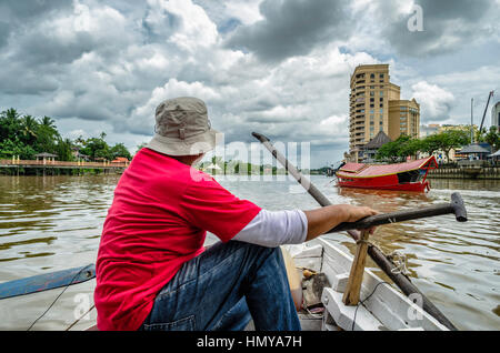 Man cruising down the river on a boat - Stock Photo