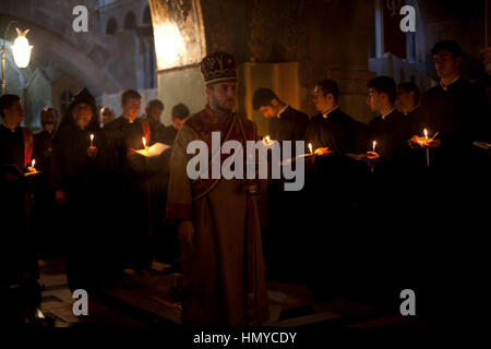 Jerusalem, Israel - May 17, 2014: Armenian priests hold a mass by the Crucifixion Altar in the Church of Holy Sepulchre - Stock Photo