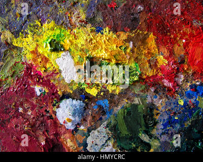 A painter's palette covered in mixed vivid paint colors. An abstract painted background. Closeup of the brush strokes - Stock Photo