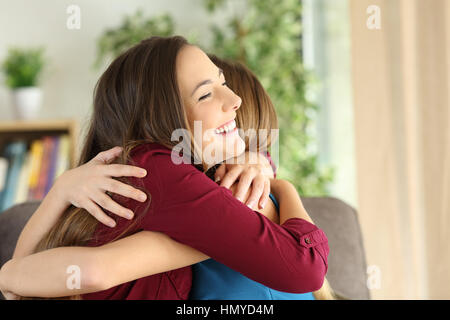Two affectionate friends or sisters embracing with love in the living room at home - Stock Photo
