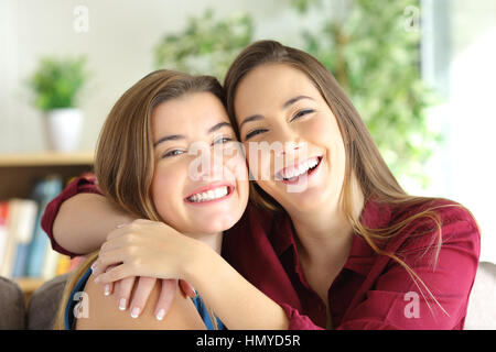 Front view portrait of a two happy friends or sisters posing smiling and looking at you with a homey background - Stock Photo