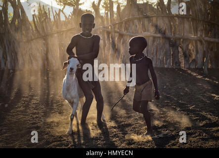 Himba boys rounding up a goat. - Stock Photo
