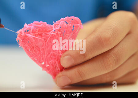 Kids hand hold heart which is made with 3D pen. Top view. Copy space for text. Selective focus - Stock Photo