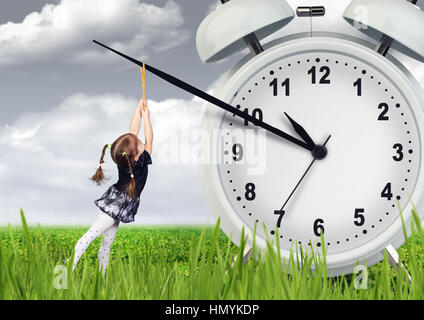 Little child girl pulling hand clock, time stop concept - Stock Photo
