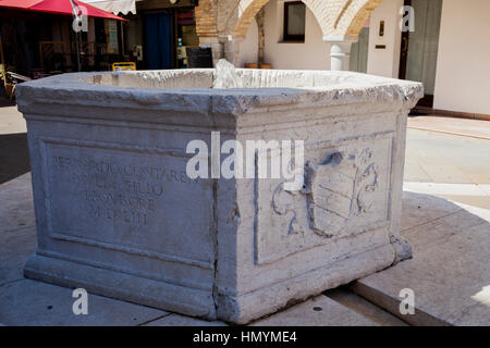 Old well with coat of arms of Marano Lagunare - Stock Photo