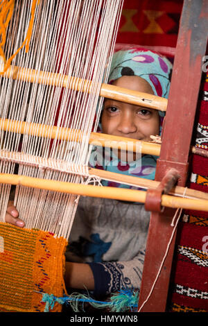 Morocco.  Young Amazigh Berber Girl Working at a Loom.  Ait Benhaddou Ksar, a World Heritage Site. - Stock Photo