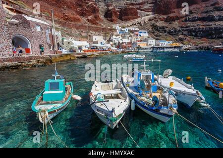 Local fishing boats moored at the foot of the cliffs at Ammoudi Bay, Oia, Santorini, a Mediterranean Greek Island - Stock Photo