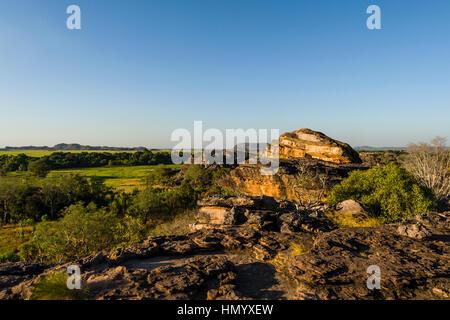 A rugged sandstone escarpment overlooking a floodplain at sunset. - Stock Photo