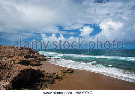 The rocky coastline and a flat beach north of Taghazout, Morocco on a sunny day. - Stock Photo