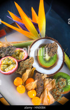 Detail of assorted dried cannabis buds with fresh tropical fruit - medical marijuana concept background - Stock Photo