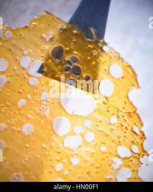 Close up of cannabis oil concentrate aka shatter with dabbing tool isolated against white background - Stock Photo