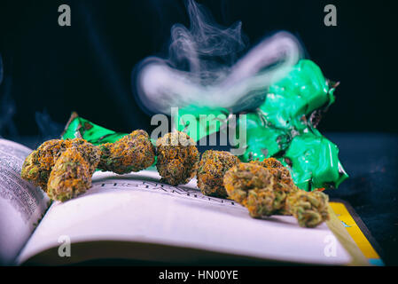 Detail of dried cannabis buds (Green Crack God strain) arranged over opened bible with smoke - medical marijuana - Stock Photo