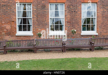 Three Georgian windows and three benches. Shot is set with a path and lawn in front of the benches and the windows - Stock Photo