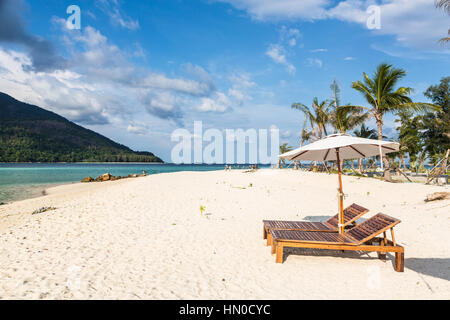 Idyllic white sand beach with long chairs and parasol in Koh Lipe island in south Thailand in the Andaman sea. - Stock Photo