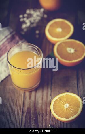 Halfed Ribera vanilla oranges and a glass of organic orange juice - Stock Photo