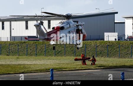 HM Coastguard helicopter, Portland, Dorset. Taking part in a patient rescue exercise. - Stock Photo