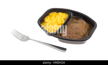TV dinner meal of salisbury steak with gravy macaroni and cheese in a black tray with a fork to the side isolated - Stock Photo