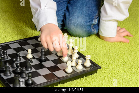 child playing chess sitting on the carpet - Stock Photo