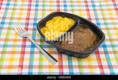 A TV dinner meal of salisbury steak with gravy macaroni and cheese in a black tray with a fork to the side on a - Stock Photo