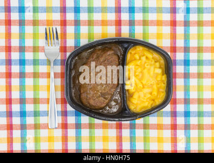 Top view of a TV dinner meal of salisbury steak with gravy macaroni and cheese in a black tray with a fork to the - Stock Photo