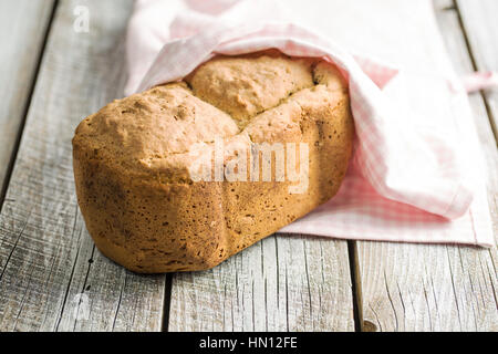 Homemade wholemeal bread on old wooden table. - Stock Photo