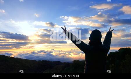 Silhouette woman raising arms and doing victory sign with the hands in the morning during sunrise on the top of - Stock Photo