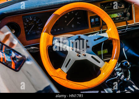 Color and beauty of vintage cars. Small wooden steering wheel of an old sport car. Dark dashboard in the background. - Stock Photo