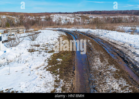 The road during the spring thaw with mud and puddles - Stock Photo