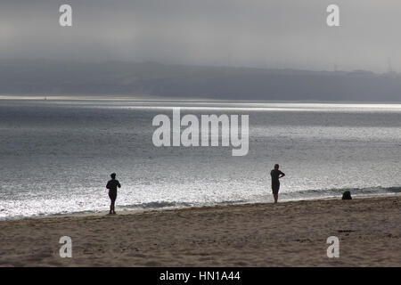 Early morning walkers and exercising on Portminster Beach , St Ives, Cornwall England UK - Stock Photo