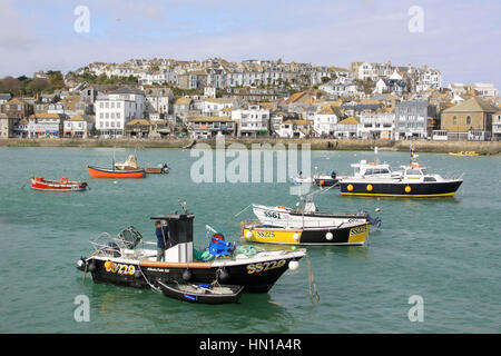 Fishing Boats moored in St Ives harbour with part of St Ives town in the background. - Stock Photo