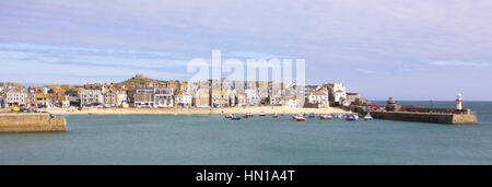 A sunny clear view of St Ives Town and the Harbour in Cornwall, England with the tide in. - Stock Photo