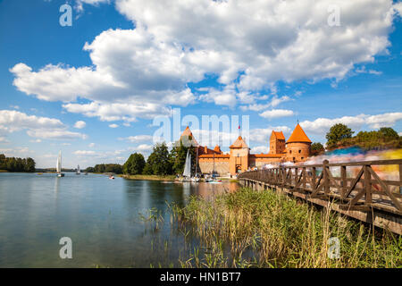Tourists visit Trakai castle in sunny siummer day, nice time to have boat trip. Long exposure, motion blur - Stock Photo
