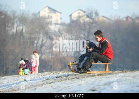 ZAGREB, CROATIA - JANUARY 15, 2017 : Two boys sledding down the hill at winter time in Zagreb, Croatia. - Stock Photo