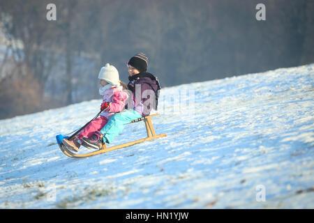 ZAGREB, CROATIA - JANUARY 15, 2017 : Two children sledding down the hill at winter time in Zagreb, Croatia. - Stock Photo
