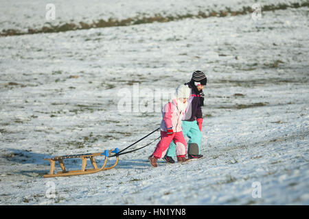 ZAGREB, CROATIA - JANUARY 15, 2017 : Two kids pulling the sledge up the hill at winter time in Zagreb, Croatia. - Stock Photo