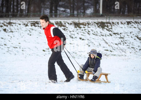 ZAGREB, CROATIA - JANUARY 15, 2017 : A boy pulling the sledge with his younger friend at winter time in Zagreb, - Stock Photo