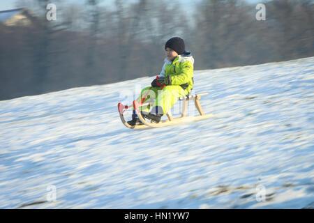 ZAGREB, CROATIA - JANUARY 15, 2017 : A child sledding down the hill at winter time in Zagreb, Croatia. - Stock Photo