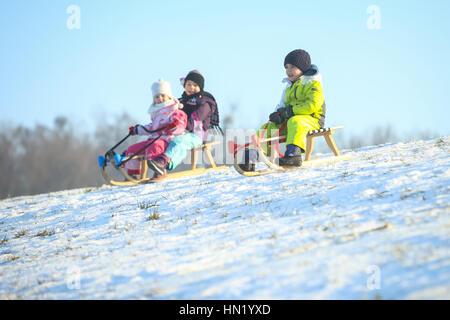 ZAGREB, CROATIA - JANUARY 15, 2017 : Children sledding down the hill at winter time in Zagreb, Croatia. - Stock Photo