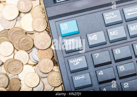 calculator and a stack of coins - Polish currency zloty - Stock Photo
