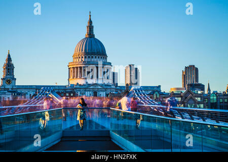 Evening light falls on the Millennium Bridge and St. Paul's Cathedral in London. - Stock Photo