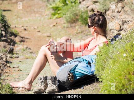 Foot massage, female hiker massaging her feet on mountain footpath. - Stock Photo
