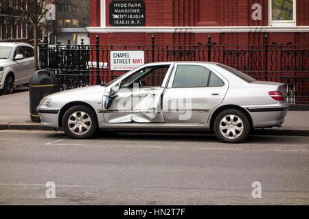Damaged car parked at the side of the road, London, UK - Stock Photo