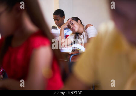 Young people and education. Group of hispanic students in class at school during lesson. Girl with headache, sick - Stock Photo