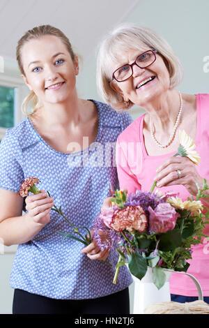 Senior Woman With Teacher In Flower Arranging Class - Stock Photo