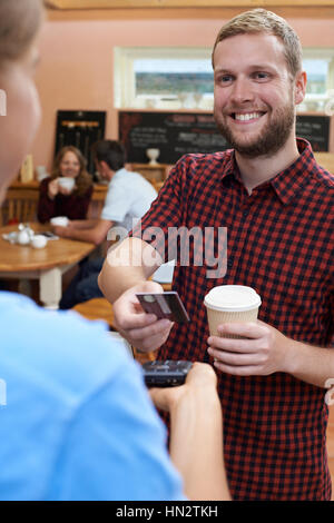 Customer Paying For Takeaway Coffee Using Contactless Terminal - Stock Photo