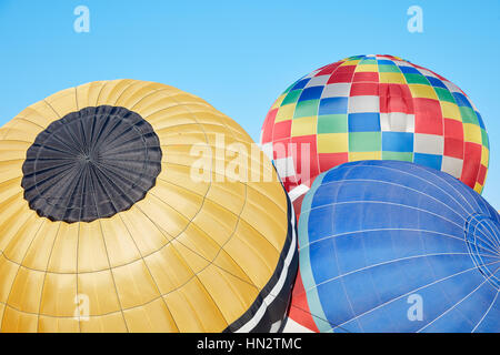 Colorful hot air balloons inflating on ground, blue sky - Stock Photo