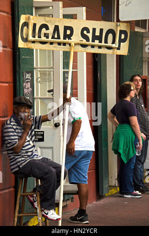 New Orleans, USA - July 13, 2015: African-American man smokes cigarette and holds an ad sign and enticing customers - Stock Photo