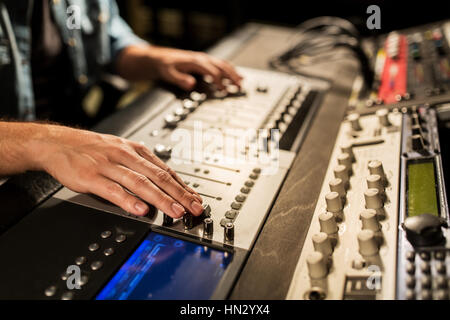 man using mixing console in music recording studio - Stock Photo