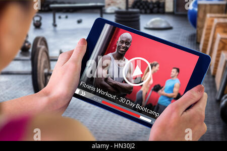 Woman using tablet pc against portrait of muscular man with arms crossed - Stock Photo
